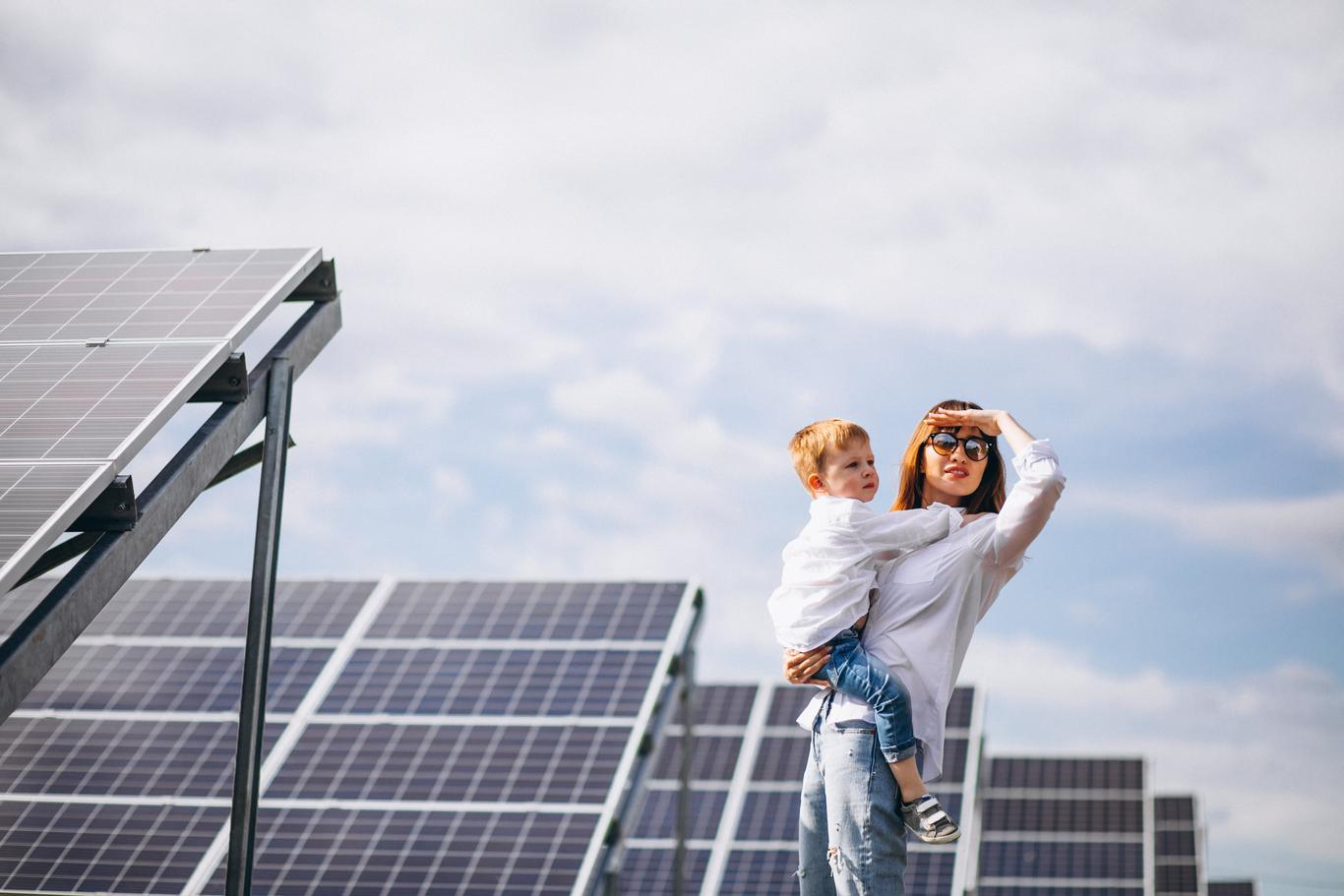 Mother with little son by solar panels